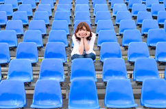 Glum woman sitting in spectator seating royalty free stock photo