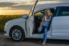 Glum woman sitting waiting for roadside assistance. Glum woman sitting in the open door of her vehicle waiting for roadside assistance at the side rural road Stock Photography