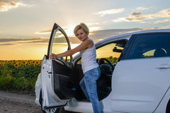 Glum woman sitting waiting for roadside assistance. Glum woman sitting open door of her vehicle waiting for roadside assistance at the side rural road  farmland Royalty Free Stock Photography