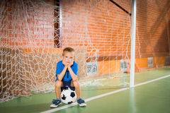 Glum young boy sitting waiting in the goalposts Royalty Free Stock Photo
