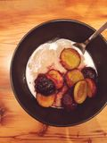 Gluten-free amaranth porridge with sautéed plums. Cooked amaranth is served with almond milk and plums that have been sautéed in coconut oil and maple syrup Royalty Free Stock Photography