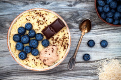 Gluten free amaranth and quinoa porridge breakfast bowl with blueberries and chocolate over rustic wooden background. Top view, overhead, flat lay. Copy space stock photos