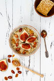 Gluten free amaranth and quinoa porridge breakfast bowl with figs, caramelized almonds, raisins and honey over rustic white table. Royalty Free Stock Image