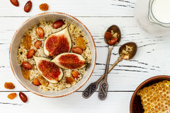 Gluten free amaranth and quinoa porridge breakfast bowl with figs, caramelized almonds, raisins and honey over rustic white table. Stock Images