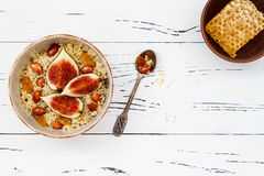 Gluten free amaranth and quinoa porridge breakfast bowl with figs, caramelized almonds, raisins and honey over rustic white table. Royalty Free Stock Images