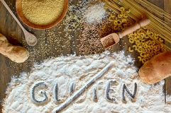 Gluten free cereals corn, rice, buckwheat, quinoa, millet, pasta and flour with scratched text gluten on brown wooden background Stock Photos