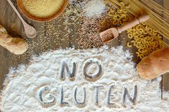 Gluten free cereals corn, rice, buckwheat, quinoa, millet, pasta and flour with scratched text no gluten on brown wooden backgroun Stock Photos