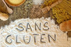 Gluten free cereals corn, rice, buckwheat, quinoa, millet, pasta and flour with text gluten free in French language on brown woode Stock Image