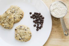Gluten free chocolate chip cookies and ingredients. Homemade gluten free chocolate chip cookies on a white plate sitting on a wooden table and some of the Stock Photo