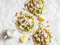 Gluten free flatbread with roasted chickpeas, cauliflower and avocado dip on a light background, top view. Healthy vegetarian food stock images