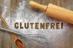Gluten free flour with text gluten free in German language with wooden spoon, beater and rolling pin on dark brown wooden backgrou. Nd,front horizontal view Stock Image