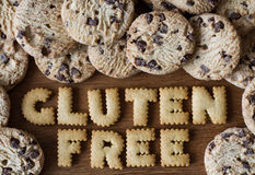 Gluten Free Food. The phrase Gluten Free spelled out with alphabet shaped cookies and surrounded by chocolate chip biscuit on a wooden table top Stock Image