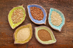 Gluten free grains bowl set. A set of five gluten free grains (sorghum, teff, amaranth,brown rice and buckwheat) - top view of leaf shape bowl against weathered Stock Photo