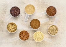 Gluten free grains in measuring scoops on wood. Gluten free grains quinoa, brown rice, kaniwa, amaranth, sorghum, millet, buckwheat, teff - a set of measuring Stock Photography
