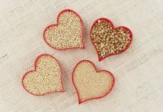 Gluten-free Grains in Red Hearts on Canvass. Four red hearts filled with gluten-free grains quinoa, millet, amaranth and buckwheat on canvass royalty free stock image