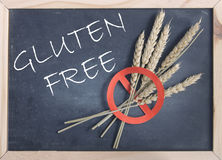 Gluten free. Handwritten on a blackboard with a red universal no sign on wheat spikes Stock Image