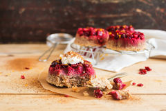Gluten free homemade cakes with fresh cranberry, whipped cream, lemon zest and cinnamon. On top on a wooden table and on the cooling rack, selective focus Royalty Free Stock Photography