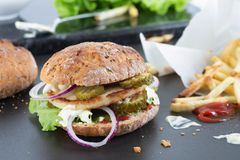 Gluten Free Homemade Halloumi Burger. Gluten free, vegetarian halloumi burger with ketchup, red onion, pickled cucumber, lettuce and creme fraiche with some royalty free stock photography