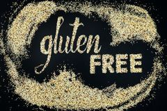 Gluten free lettering made of quinoa. Black background. Flat lay Stock Photos