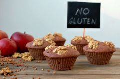 Gluten free muffins from buckwheat flour, apple, cinnamon and walnuts on brown wooden background with index card with text no glut Stock Image
