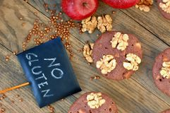 Gluten free muffins from buckwheat flour, apple, cinnamon and walnuts on brown wooden background with index card with text no glut Stock Images