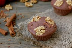 Gluten free muffins from buckwheat flour, apple, cinnamon and walnuts on red cloth on brown wooden table with black background Stock Photography