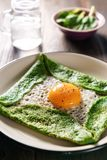 Gluten free spinach crepe with fresh egg on a wooden background. Glass mug with water and spinach leaves in bokeh Stock Photography