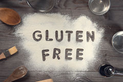 Gluten free. Word gluten free written in white flour on a old wooden table from top view in vintage tone, surrounding by baking tools Royalty Free Stock Photo