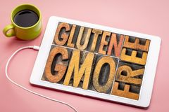 Gluten and GMO free banner in wood type. Gluten and GMO genetically modified organism free banner  - word abstract in vintage on a digital tablet with a cup of royalty free stock photography
