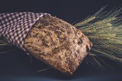 Gluten-gratuit fait maison et sans pain d'artisan de levure avec des oreilles d'orge enveloppées dans la serviette à carreaux Photographie stock libre de droits