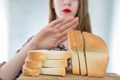 Gluten intolerance concept. Young girl refuses to eat white brea Royalty Free Stock Photo