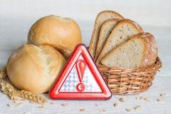 Gluten nietolerancyjność z chlebową banatką i znak ostrzegawczy na białych deskach Obraz Royalty Free