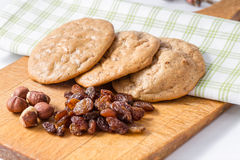 Gluten's cookies with raisins and hazelnuts. Three cookies on a napkin and dried fruit on the front Stock Photo
