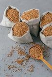 Gluten Vrij Product Verticaal die van droog bruin boekweit voor vegetariërs wordt geschoten Zakken met graangewassen Houten lepel stock fotografie