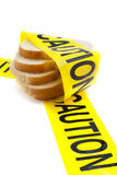Gluten and wheat allergy warning. Slices of bread wrapped in yellow caution tape, dietary warning or gluten/wheat allergy warning Stock Photography
