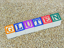 Gluten. In wheat concept, illustrated through the letters g, l, u, t, e and n carved on wooden blocks Royalty Free Stock Images