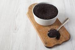 Glutenu bezpłatny surowy organicznie czarny quinoa na nieociosanej drewnianej desce nad białym drewnianym tłem, niskiego kąta wid zdjęcia stock