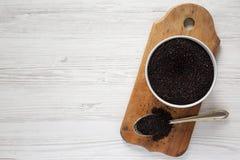 Glutenu bezpłatny surowy organicznie czarny quinoa na nieociosanej drewnianej desce, zasięrzutny widok Mieszkanie nieatutowy, odg zdjęcia stock