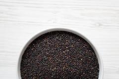 Glutenu bezpłatny surowy organicznie czarny quinoa w pucharze nad białym drewnianym tłem, odgórny widok Od above, koszt sta?y, mi fotografia royalty free