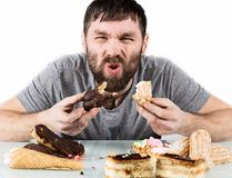 Glutton bearded man eating cupcakes with frenzy after long diet. Harmful but delicious food royalty free stock photography