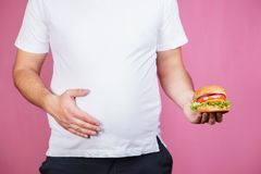 Glutton man with burger. hunger, unhealthy diet. Glutton man eating tasty burger. imbalanced ration, snacking with fast food, unhealthy diet stock photos