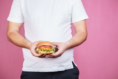 Glutton man eating burger, unhealthy diet. Glutton man eating tasty burger. imbalanced ration, snacking with fast food, unhealthy diet royalty free stock photo