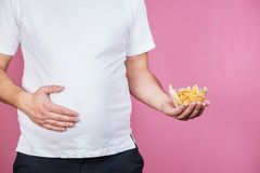 Glutton man with fast food, unhealthy diet. Weight loss, overweight, plus size, diet, unhealthy eating. fat woman with portion of french fries stock photography