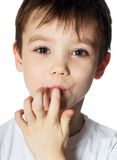 Glutton. A young boy licks his fingers after eating. Image on white background stock photography