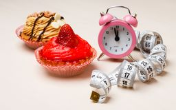 Sweet food measuring tape and clock on table Royalty Free Stock Image