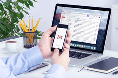 Gmail app na iPhone pokazie w mężczyzna rękach na Macbook ekranie i Fotografia Stock