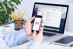 Gmail app på iPhoneskärm i manhänder och på den Macbook skärmen Arkivbild