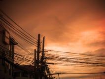 Gmatwanina kabel i elektryczności poczta na zmierzchu tle Zdjęcia Stock
