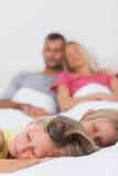 Gêmeos que dormem na cama na frente de seus pais Foto de Stock
