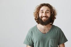 Gmeranie pozytyw w everything Portret szczęśliwy atrakcyjny wschodni mąż z kędzierzawym włosy i broda w zieleni t obraz royalty free